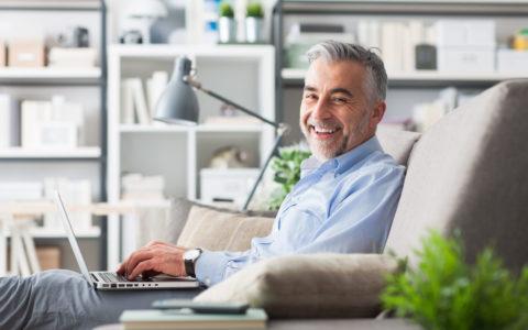 Uśmiechnięty biznesmen siedzący na kanapie u siebie w domu, pracujący na swoim laptopie.