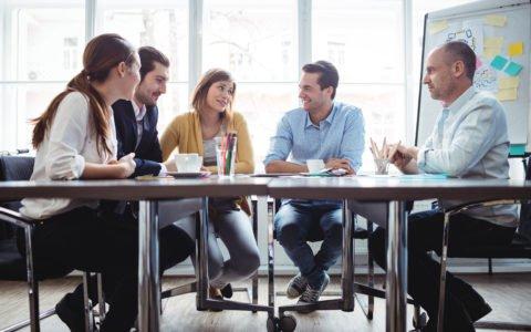 Piątka ludzi siedząca przy jednym biurku pracująca przy czymś w firmie.