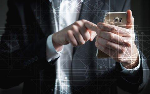 Elegancko ubrany mężczyzna korzystający z technologi 5G na swoim telefonie.