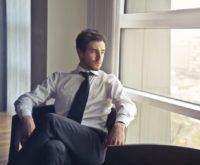 Elegancko ubrany mężczyzna siedzący w swoim biurze z ponurą twarzą. Wyglądający na wypalonego
