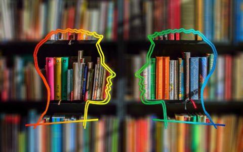 Dwa kontury twarzy skierowanych ku sobie na tle regału z książkami