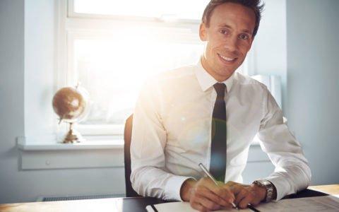 Elegancko ubrany mężczyzna siedzący przy biurku generujący zysk dla swojej firmy.