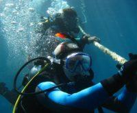 Dwóch nurków pod wodą trzymających line.