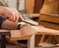 Obrazek ukazuje ręce cieśli podczas pracy nad obróbką drewna