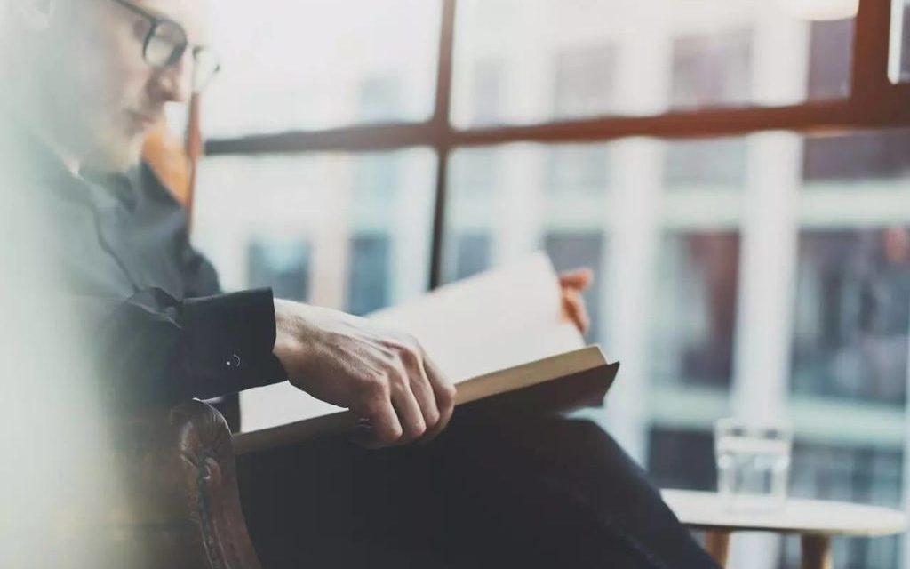 Mężczyzna na fotelu czytający książkę zmieniającą jego życie