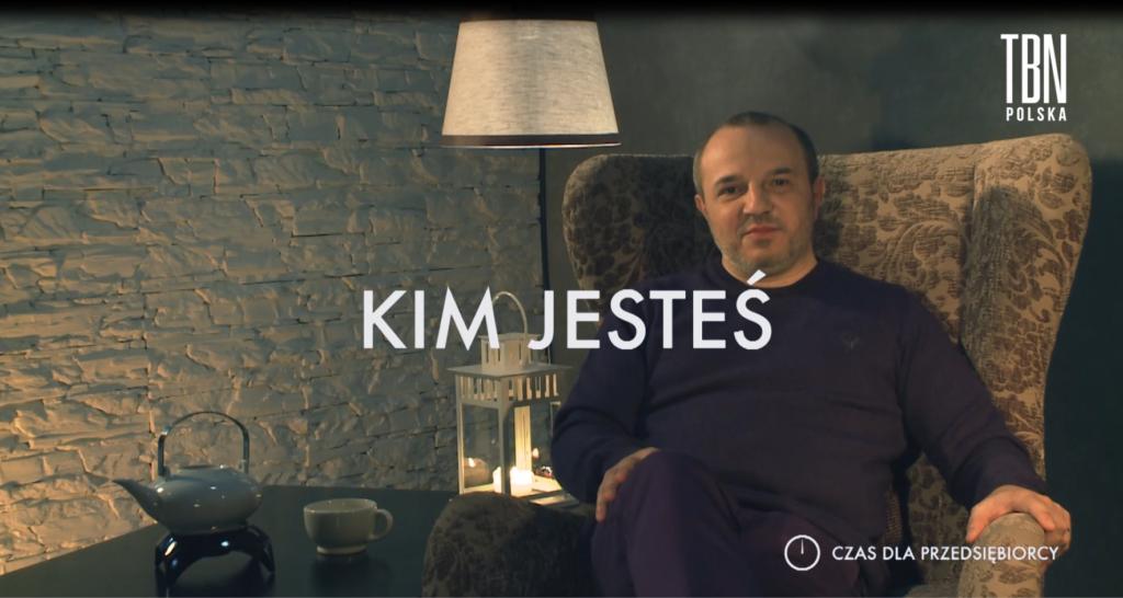"""Na pierwszym planie po środku napis """"Kim jesteś"""". Za nim siedzący na fotelu Andrzej Burzyński"""