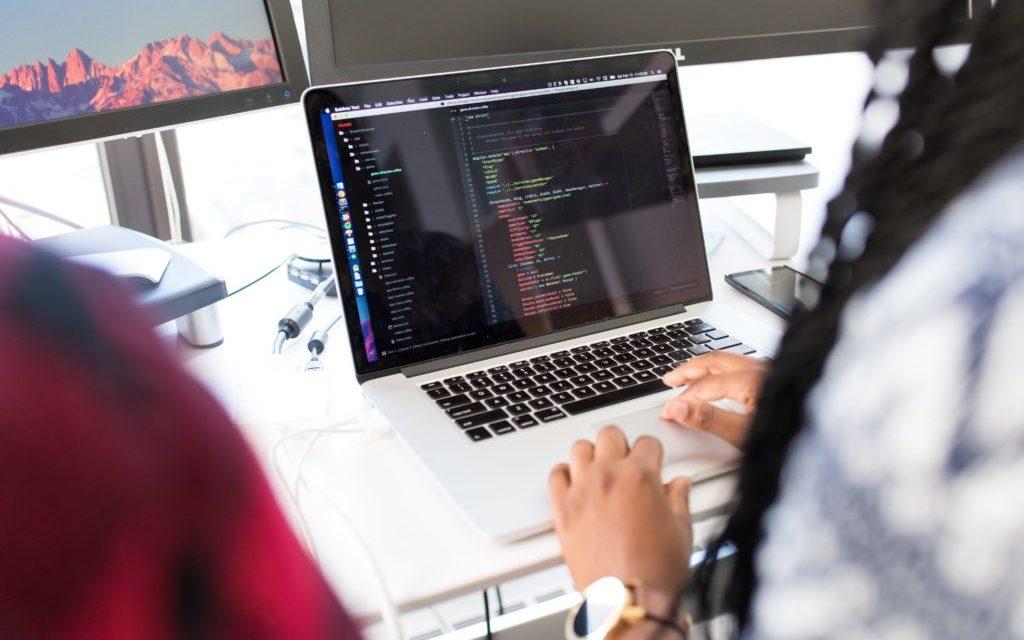 Przestrzeń biurowa stoimy za plecami osoby korzystającej z wolnego oprogramowanie w biznesie używając do tego laptopa.