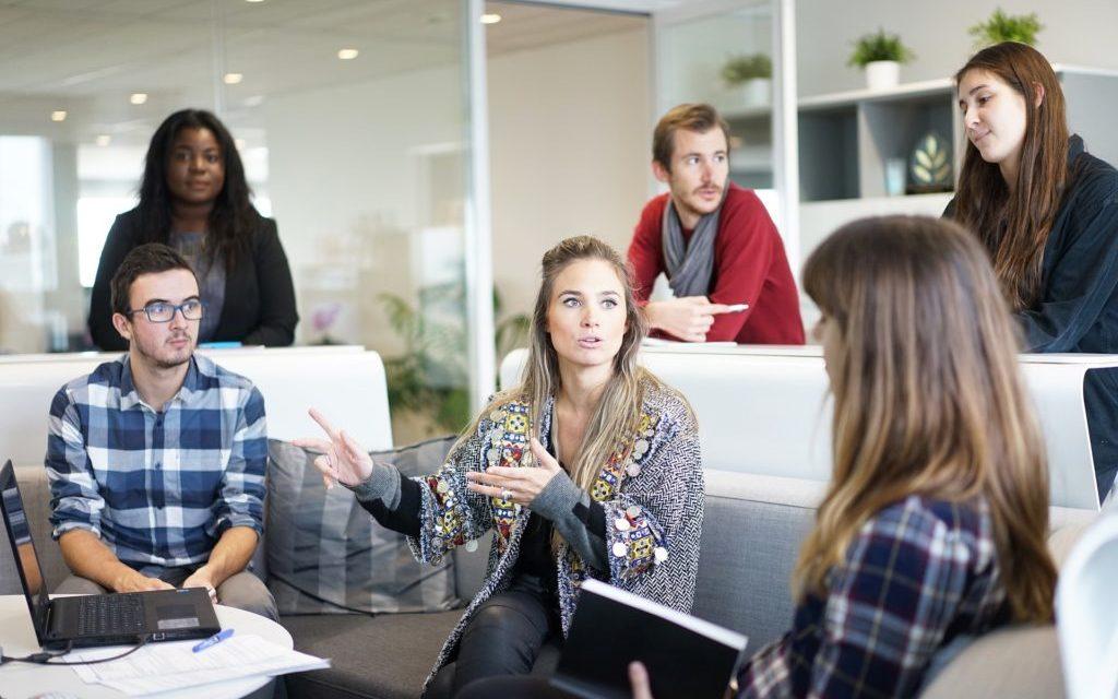 Grupa ludzi w biurze pracująca nad jakimś projektem. W środku między nimi znajduję się kobieta wydająca się być liderem zespołu.