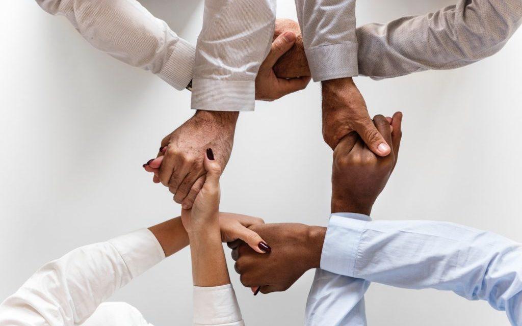 Czwórka ludzi trzymających się za skrzyżowane ręce symbolizujących relacje