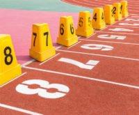 Na tartanowym torze do biegania ustawione osiem pachołków symbolizujących osiem dróg do bogactwa.