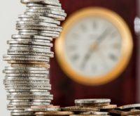 Wyostrzona wieża z monet a za nią już niewyraźny zegar, symbolizujący czas na spłacanie długu.