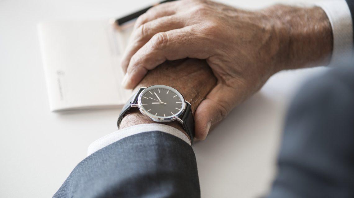 Skrzyżowane ręce elegancko ubranego mężczyzny. Na lewej dłoni zegarek symbolizujący czas.