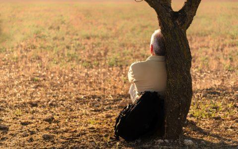Znudzony starszy Pan siedzący pod drzewem i wpatrujący się w przestrzeń.
